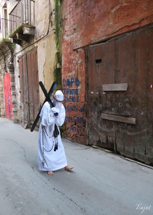 valkoisiin pukeutunut henkilö kantaa ristiä pääsiäisenä pugliassa
