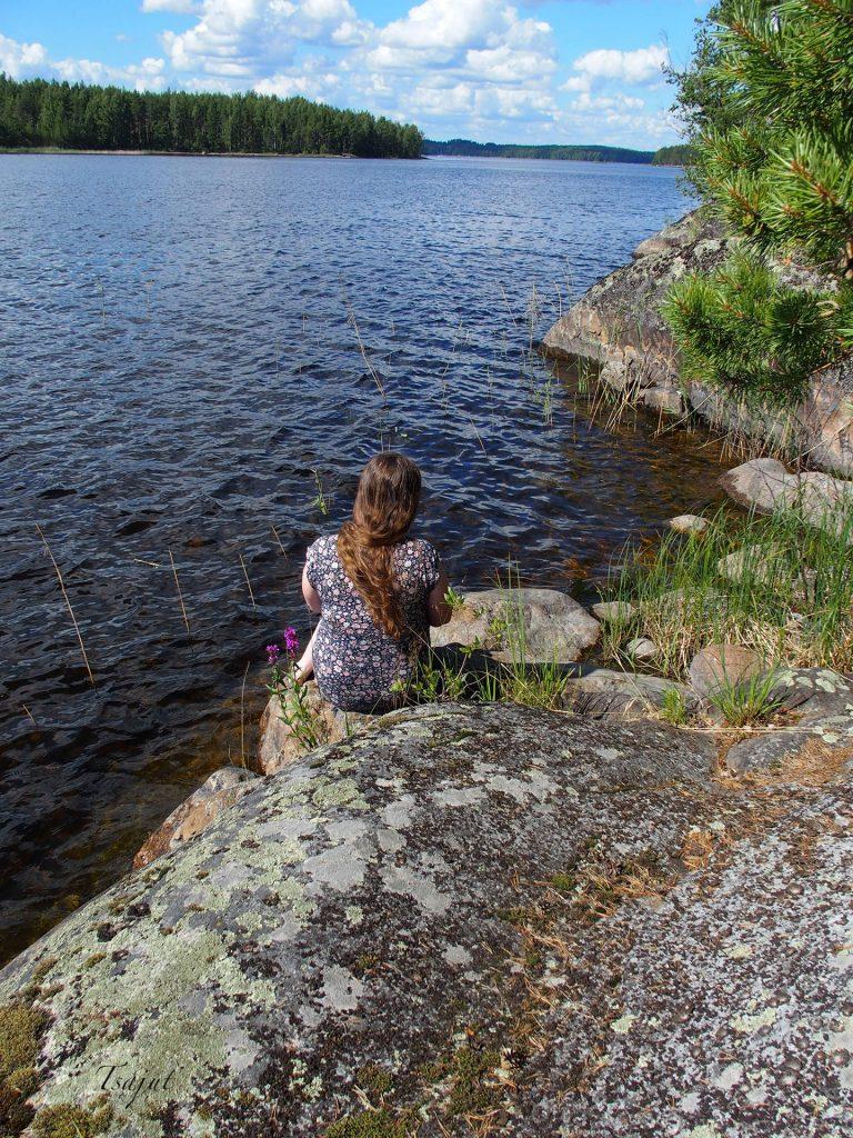 rantakalliolla istuu nainen ja katsoo järvelle
