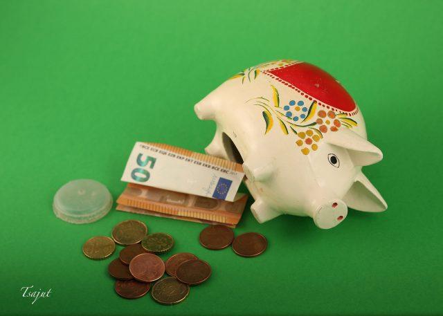 säästöpossu avattuna kolikot ja seteli esillä