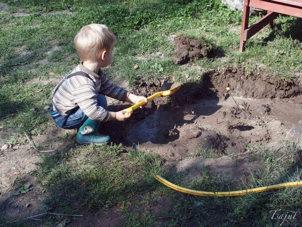 lapsi kaivaa kuoppaa lapiolla
