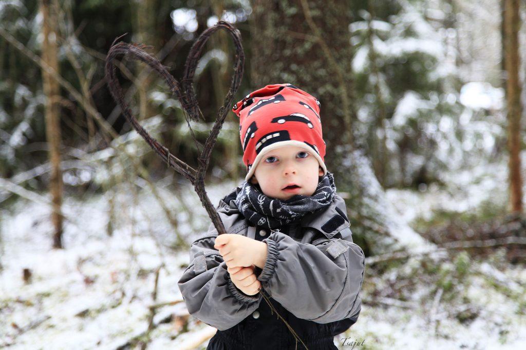 punapipoinen lapsi pitelee risusydäntä metsässä